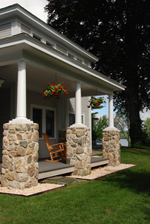 wood and stone columns provide beautiful support for this home's entrance